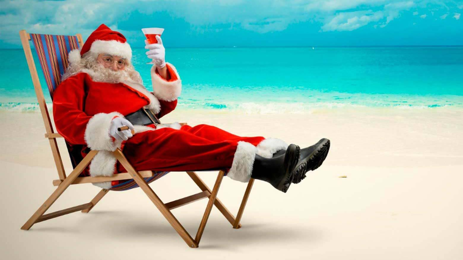 Father Christmas on a beach sitting in a deckchair